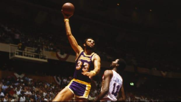 Kareem Abdul-Jabbar doing his signature skyhook against a defender