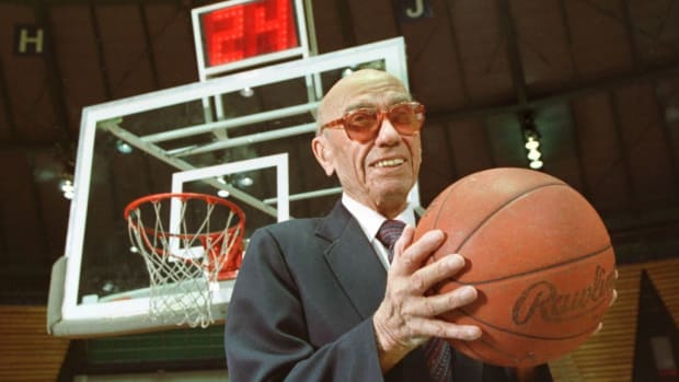 The late Danny Biasone, an innovator of the 24-second shot clock for professional basketball, is shown in this March 8, 1992 photograph at a gym at Syracuse University in Syracuse, N.Y. Behind him is a modern shot clock. Biasone and other National Basketball Association owners met in Syracuse in 1954 and tested the 24-second clock at a basketball game in a local school. That decaying school now is reaching out to the NBA for a donation.  (AP Photo/Michael Okoniewski)